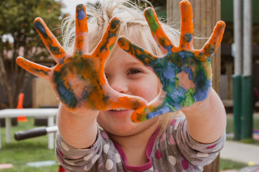 Creativity in Education. Girl with paint on hands.