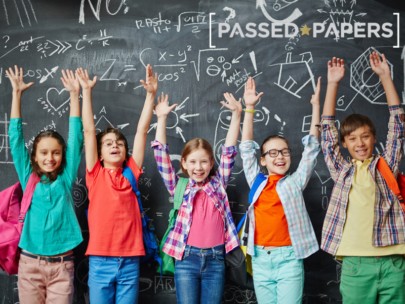 Keystage 2 SATS. Children in front of blackboard with arms in the air.