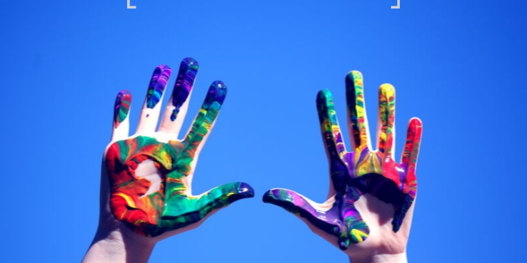 Ambidextrous children – Learning disorder or gift? Two hands with paint on in the air.