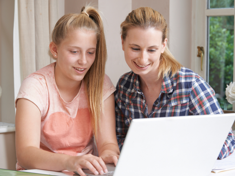 Mom and daughter busy with online tutoring.