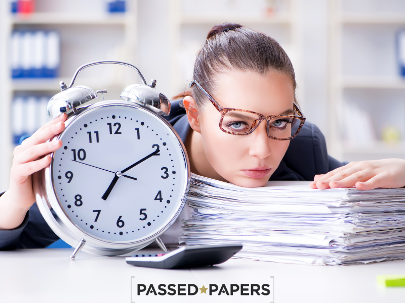 Woman with clock and pile of papers time management skills